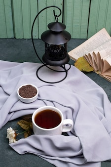 A cup of tea and herbs in a saucer on the table, a book around
