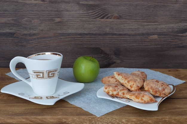 A cup of tea, homemade cookies and an apple on a background of wooden boards.