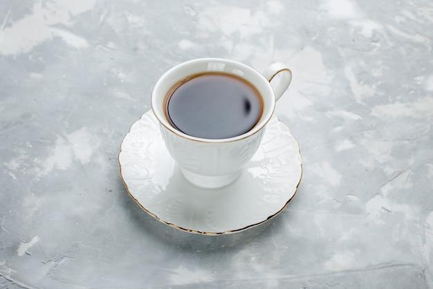 Tazza di tè caldo all'interno della tazza bianca sulla luce, bevanda del tè dolce