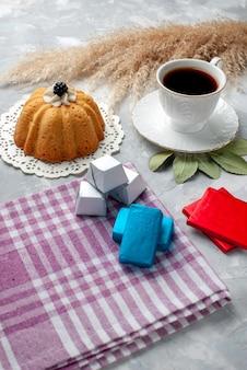 Tazza di tè caldo all'interno della tazza bianca con cioccolatini torta sulla scrivania leggera, tè al cioccolato caramelle zucchero dolce cuocere