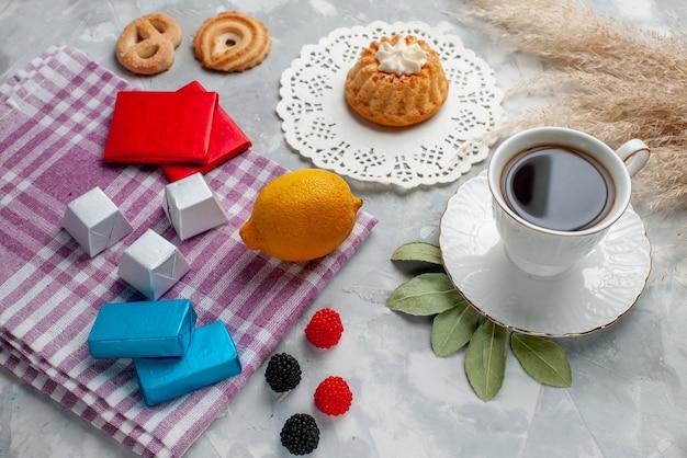 Cup of tea hot inside white cup with cake lemon chocolates on light,  tea chocolate candy cake