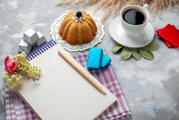 Tazza di tè caldo all'interno della tazza bianca con cioccolatini blocco note torta sulla scrivania leggera, caramelle al cioccolato tè dolce