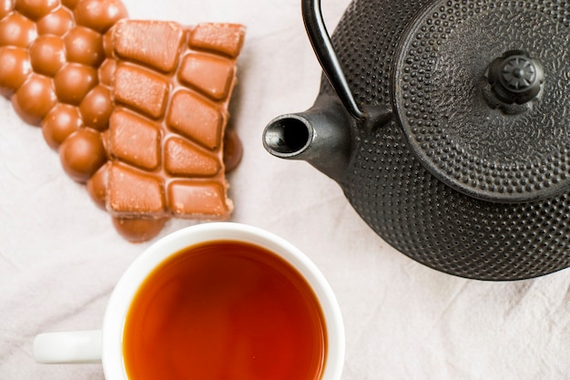 Cup of tea, iron teapot and chocolate bars