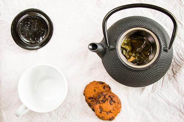 Cup of tea, iron teapot and cookies Premium Photo