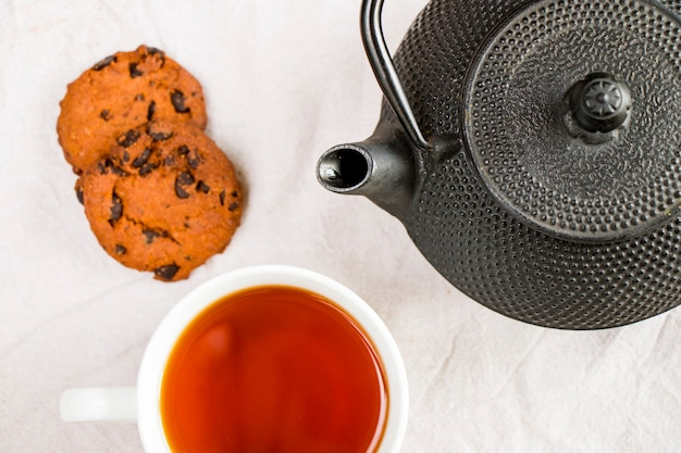 Cup of tea, iron teapot and cookies
