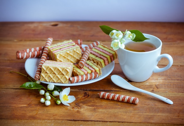 Cup of tea and jasmine flowers, plate with slices of biscuit cake and cookies