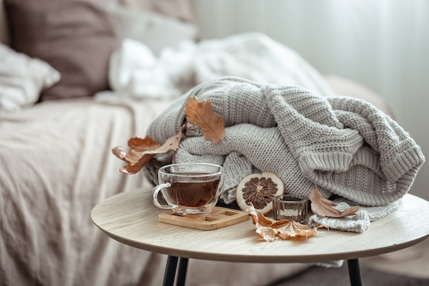 A cup of tea, a knitted element and dry autumn leaves on a blurred background.