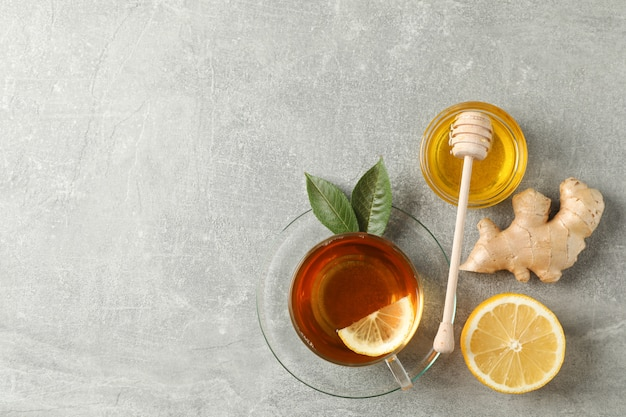 Cup of tea, leaves, ginger, lemon, honey and dipper on grey, top view
