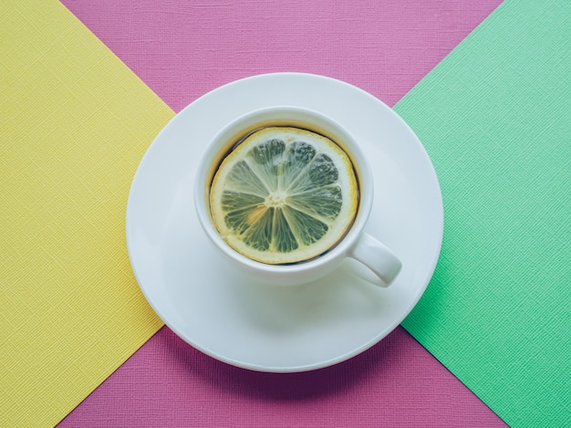Cup of tea and lemon. colorful paper background.