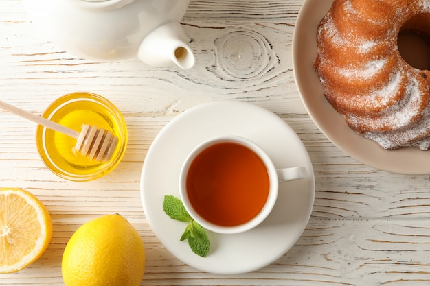 Cup of tea, lemon, mint, honey, dipper and pie on wooden, top view