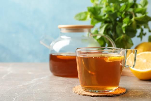 Cup of tea, lemon, teapot and mint on grey, close up