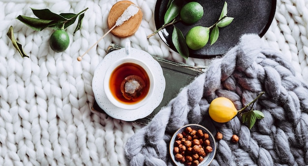 A cup of tea, lemon and a white blanket. instagram. view from above. long banner