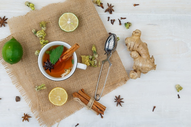 Cup of tea, limes, a tea strainer cinnamon in linen placemat with ginger on grey surface