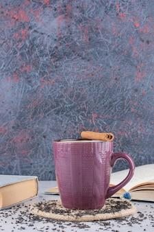 Tazza di tè sul tavolo di marmo con cannella e libri. foto di alta qualità