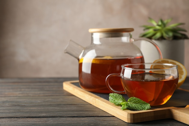 Cup of tea, mint, honey, ginger and teapot on wooden, space for text