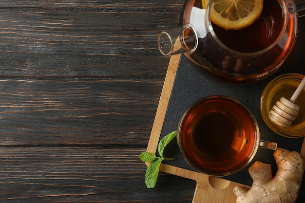 Cup of tea, mint, honey, ginger and teapot on wooden, top view
