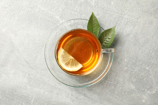 Cup of tea, mint and lemon on grey, top view