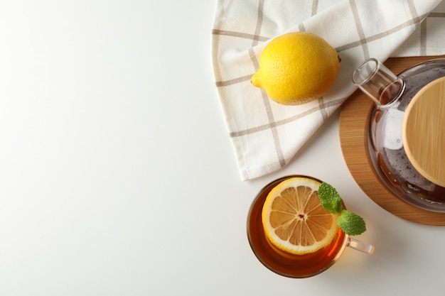 Cup of tea, mint, lemon, tea pot and towel on white, copy space