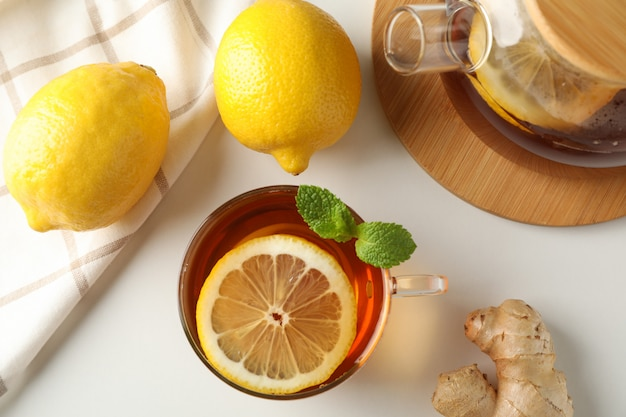 Cup of tea, mint, lemon, tea pot and towel on white, top view