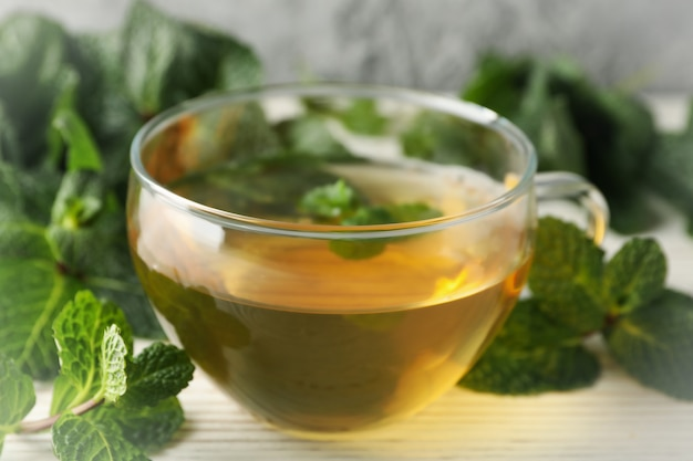 Cup of tea and mint on white wooden table, close up