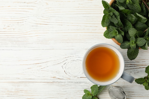 Cup of tea and mint on white wooden table, space for text