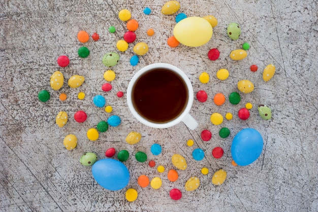 Cup of tea between mix of candies and eggs