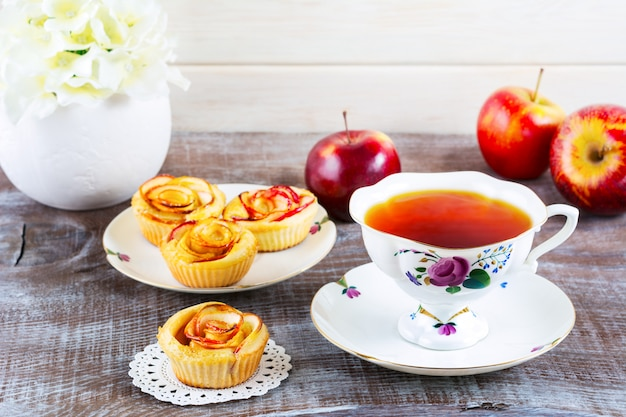 Cup of tea and muffins with rose shaped apple slices