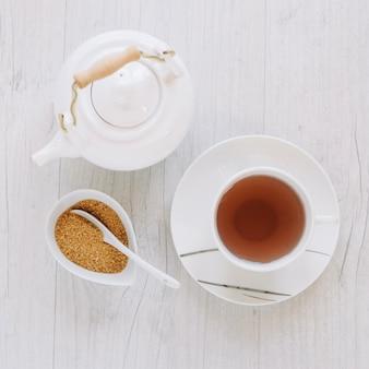 Cup of tea near sugar and teapot