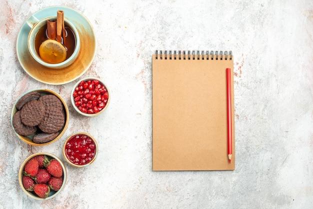 Una tazza di tè quaderno matita una tazza di tè ciotole di biscotti alla marmellata di frutti di bosco
