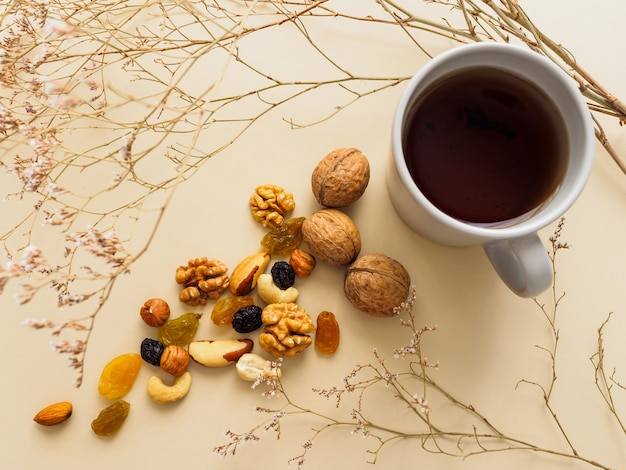 Cup of tea, nuts and raisins next to dried flowers