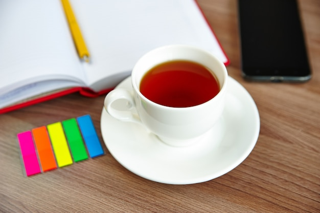 A cup of tea and an open notebook, a mobile phone on a wooden table