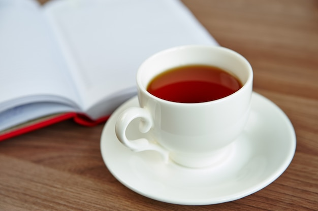 A cup of tea and an open notebook on a wooden table, a selective focus