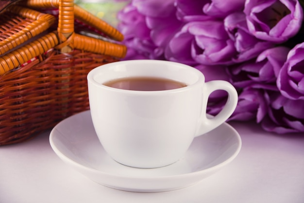 A cup of tea, picnic basket and violet tulips on the table