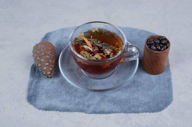 Cup of tea, pinecone and grains on marble background. high quality photo