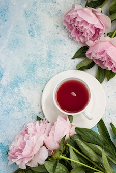 Cup of tea and pink peonies flowers