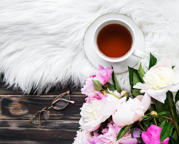 Cup of tea and pink peonies