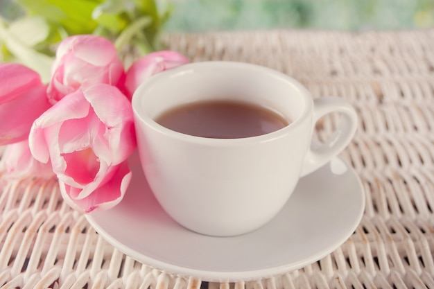 A cup of tea and pink tulips on the table