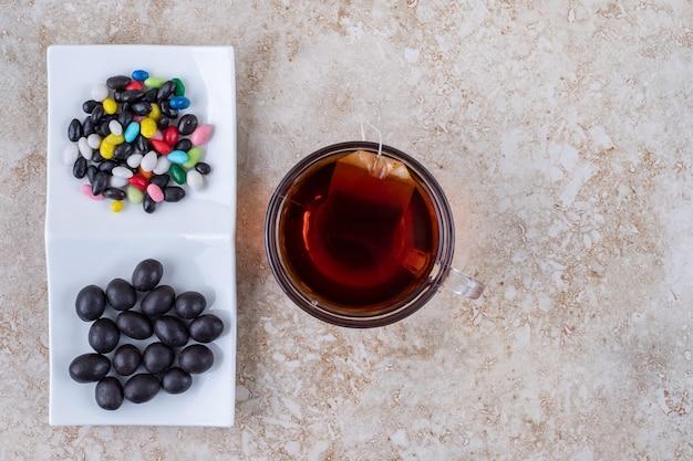 Tazza di tè e piatto di cioccolatini su superficie di marmo