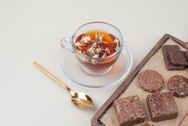 Tazza di tè e piatto di biscotti al cioccolato sulla superficie bianca