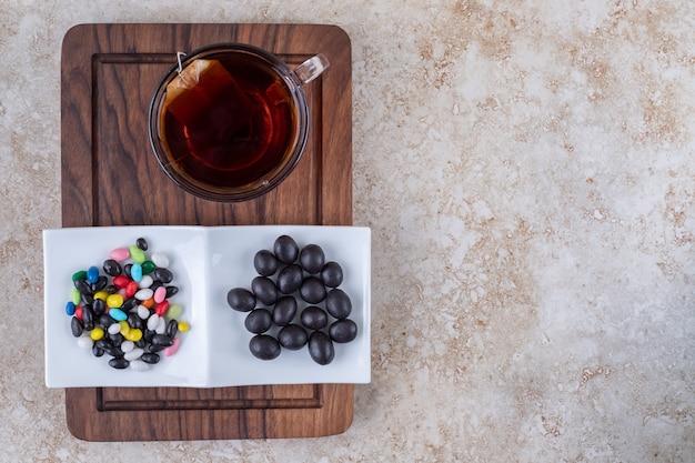 Tazza di tè e piatto di cioccolatini su tavola di legno
