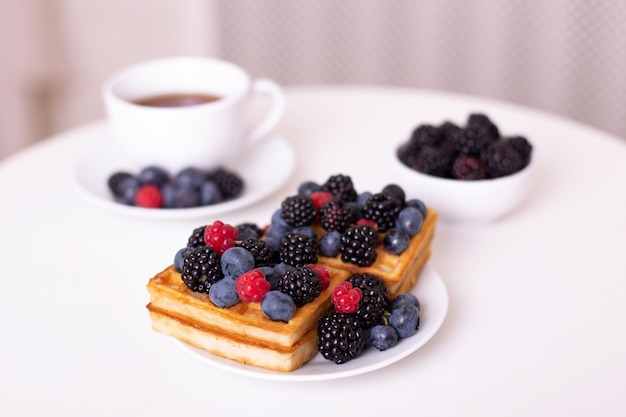 Cup of tea, plate with waffles, blueberries on white background