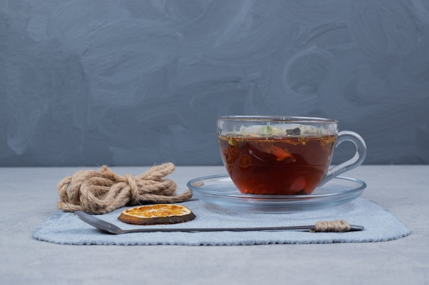 Cup of tea, rope and mandarin slice on marble table. high quality photo
