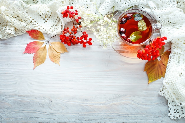 A cup of tea and rowan berries on a wooden table. autumn still-life.