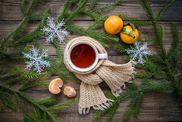 Cup of tea in scarf and christmas decoration background