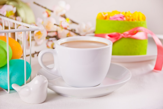 A cup of tea, small spring cake, flowers sakura, colorful eggs for easter day. spring concept.