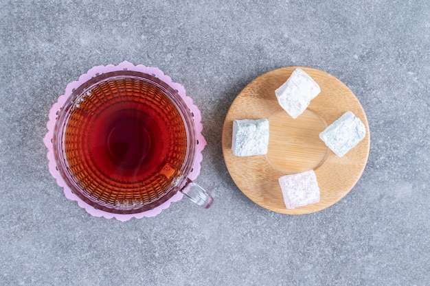 Cup of tea and soft candies on marble surface