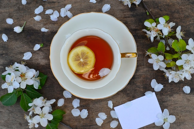 Cup of tea and spring apple blossoms on a wooden surface with copy space. top view.