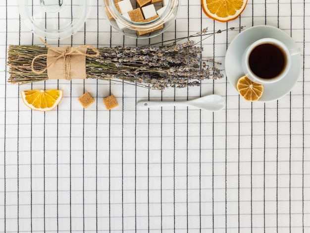 Cup of tea and sugar bowl on a checkered tablecloth top view