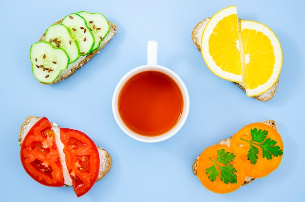 Cup of tea surrounded by assorted sandwiches