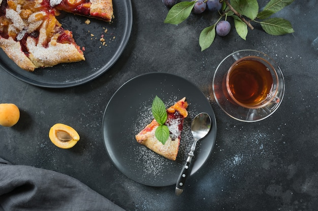 Cup of tea and tasty fall pie galette with plum and apricot on black table.